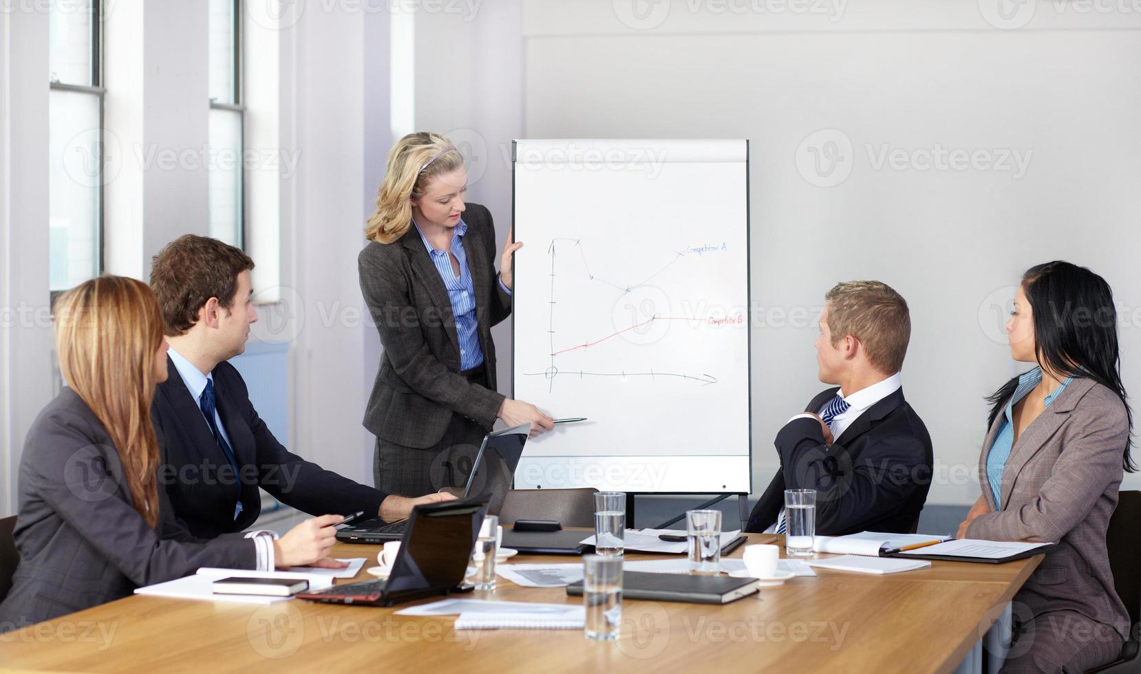 grafico presente femminile biondo sulla lavagna a fogli mobili durante la riunione d'affari foto