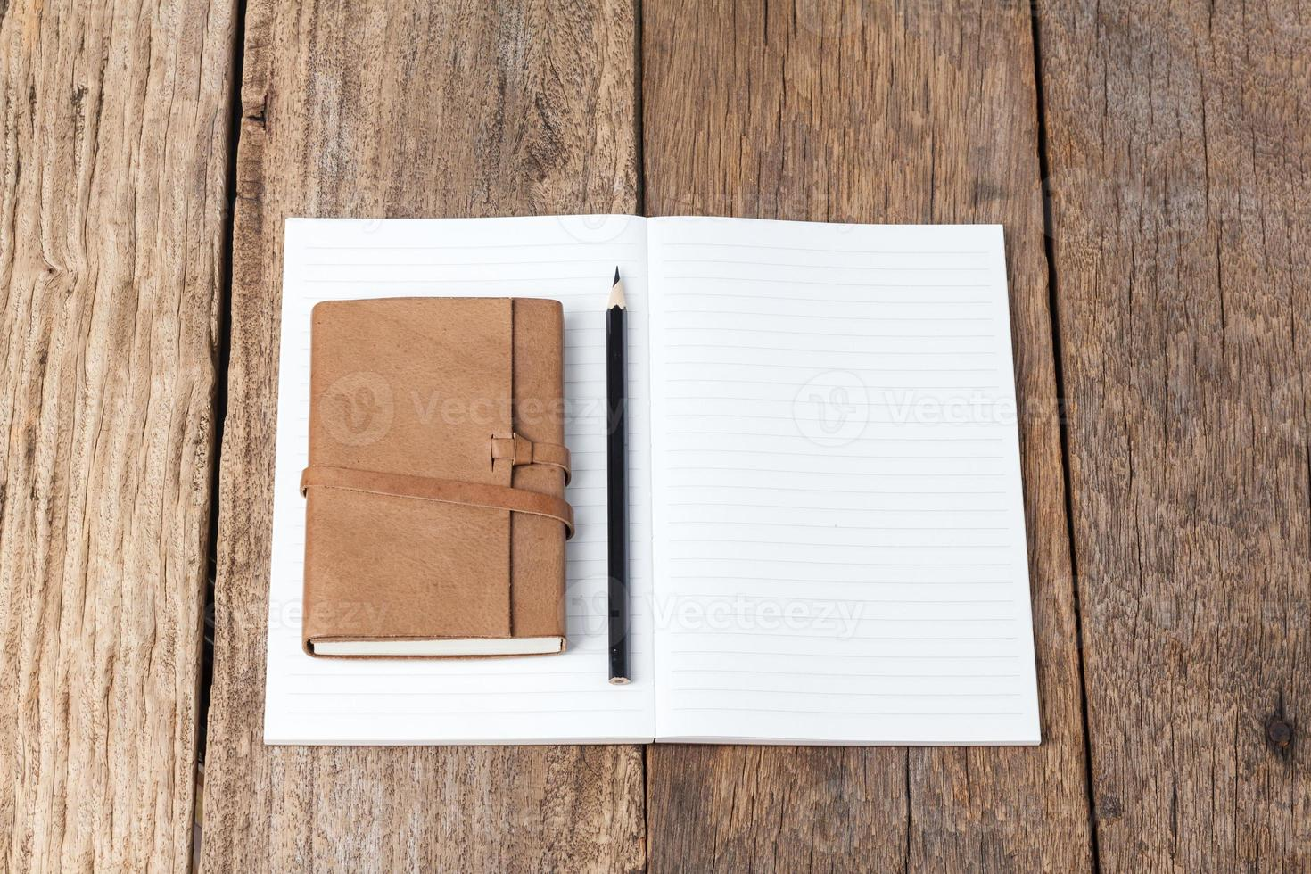 taccuino in bianco aperto con la matita nera sulla tavola di legno foto