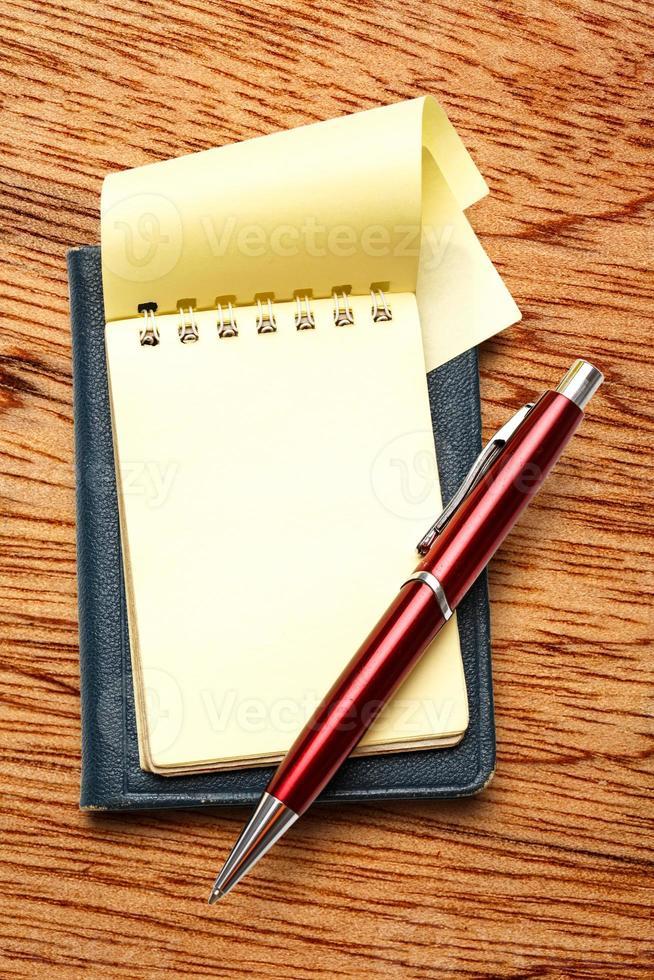 blocco note bianco giallo con penna foto