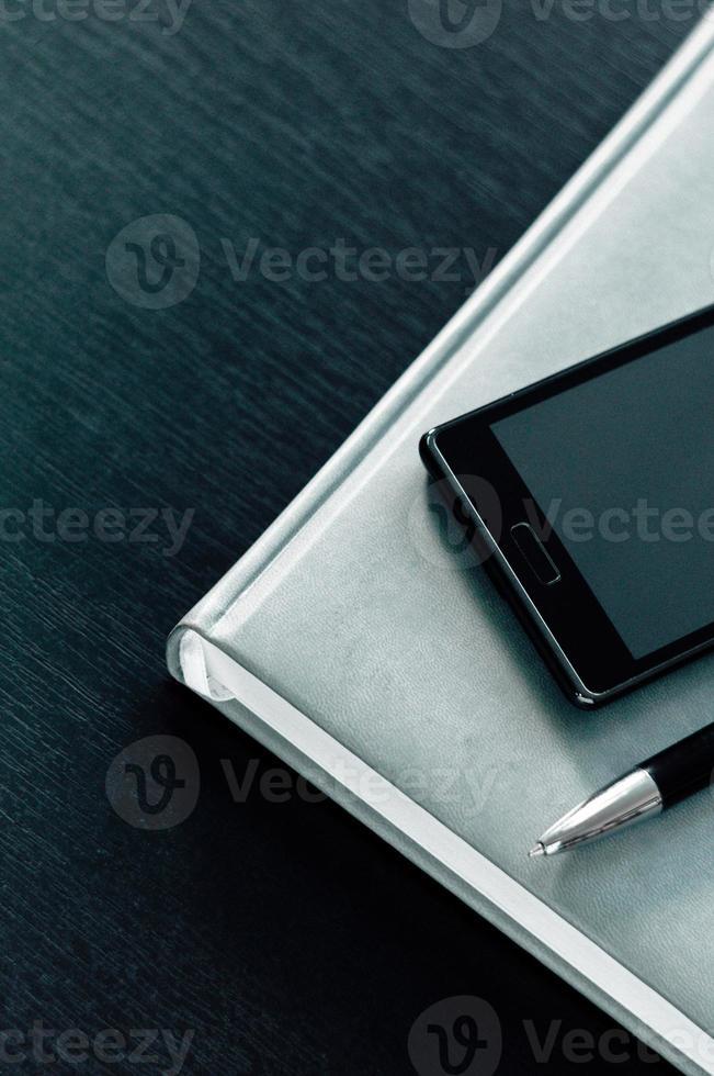 planner con telefono su uno sfondo nero foto