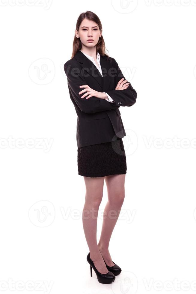 attraente fiduciosa giovane imprenditrice bruna in piedi con le braccia incrociate foto