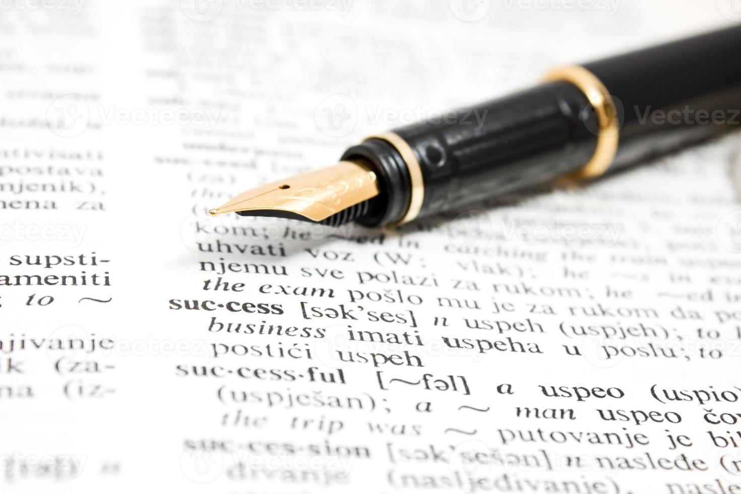 penna stilografica e libro del dizionario foto