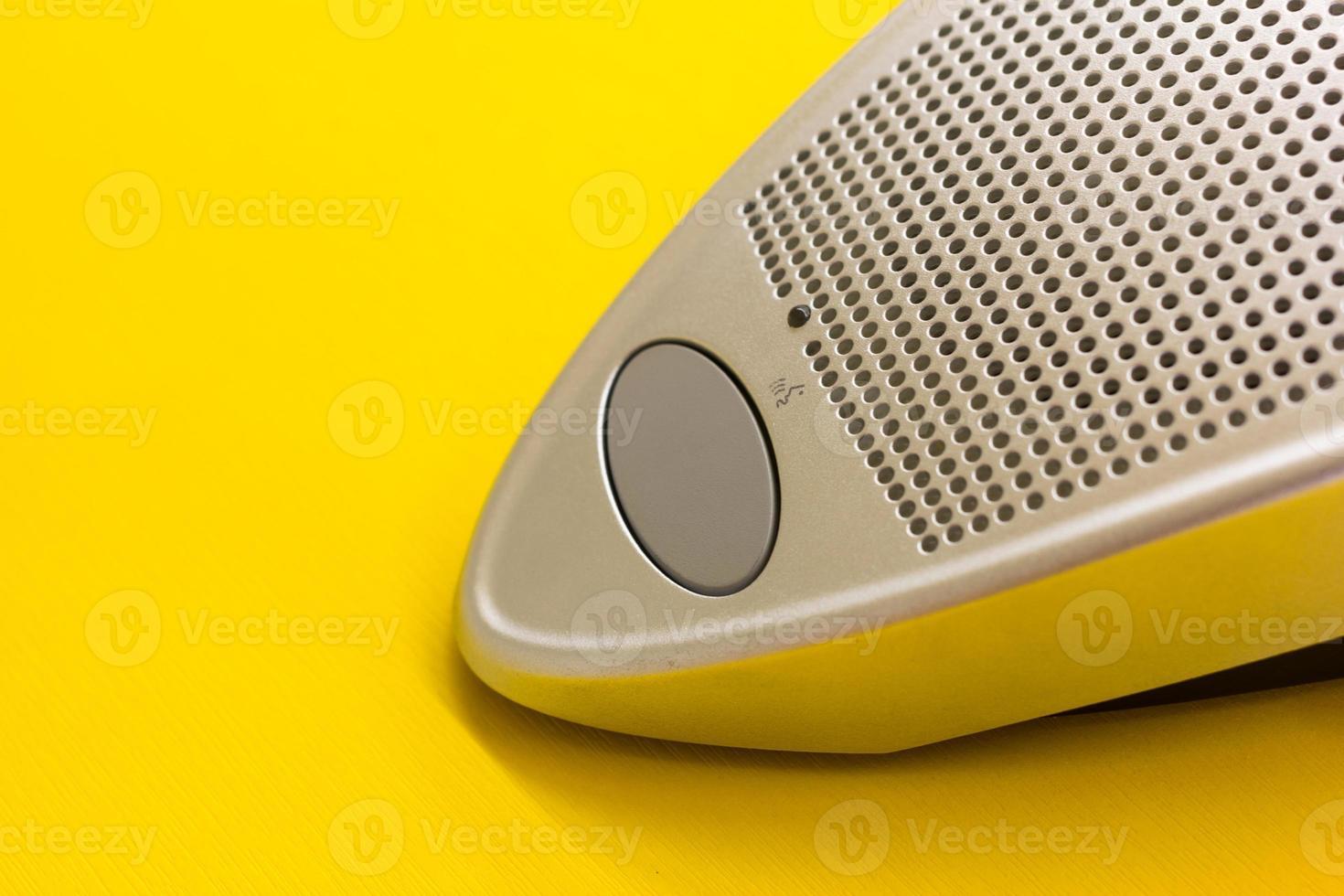 pulsante altoparlante microfono sul tavolo giallo foto