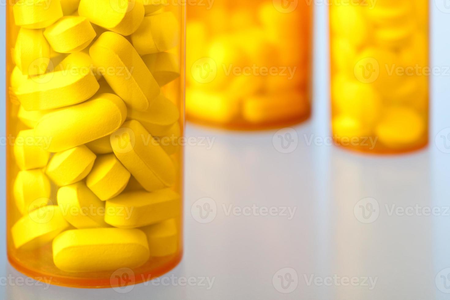 primo piano di bottiglie di medicina di prescrizione contenenti pillole e compresse foto