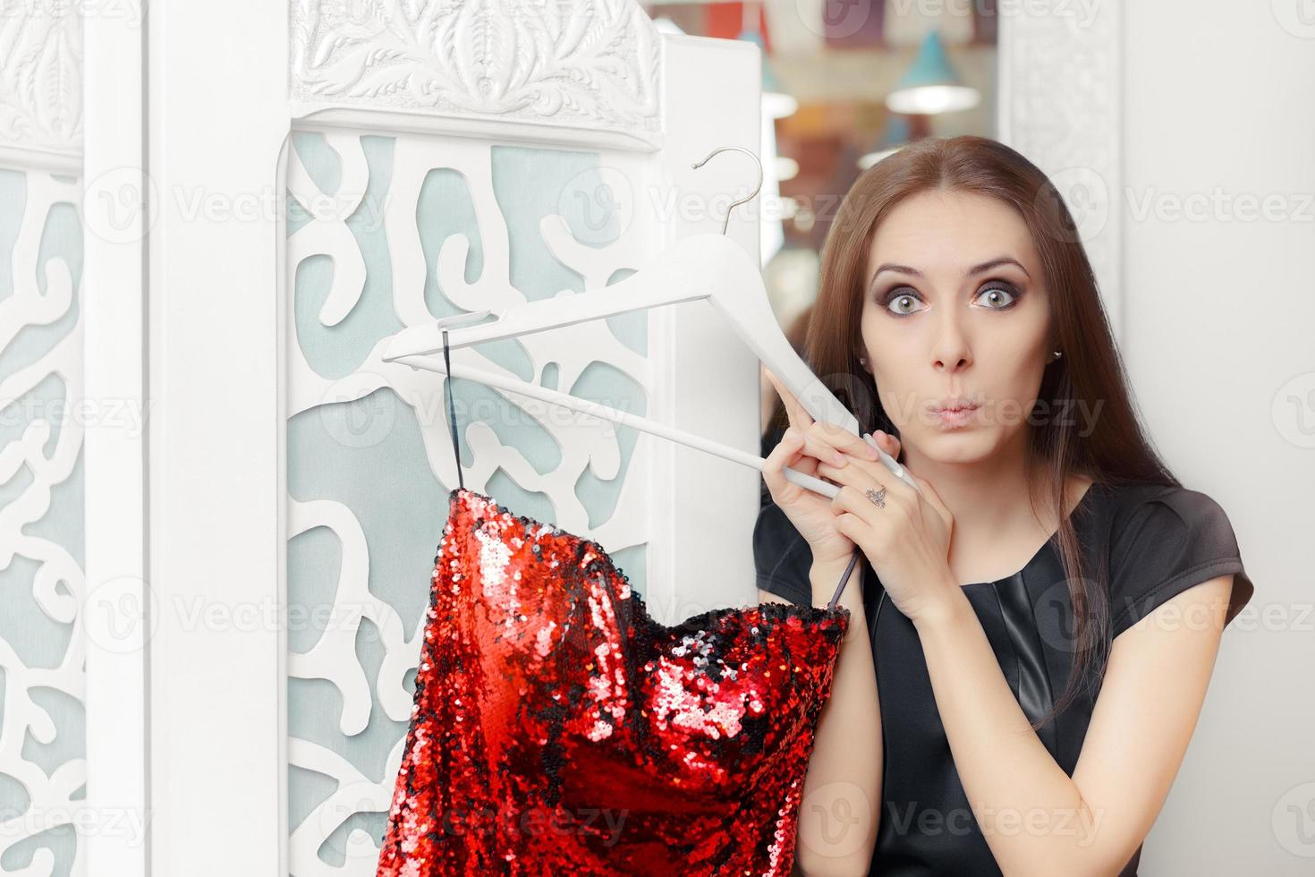 ragazza stupita che prova il vestito da festa rosso nello spogliatoio foto