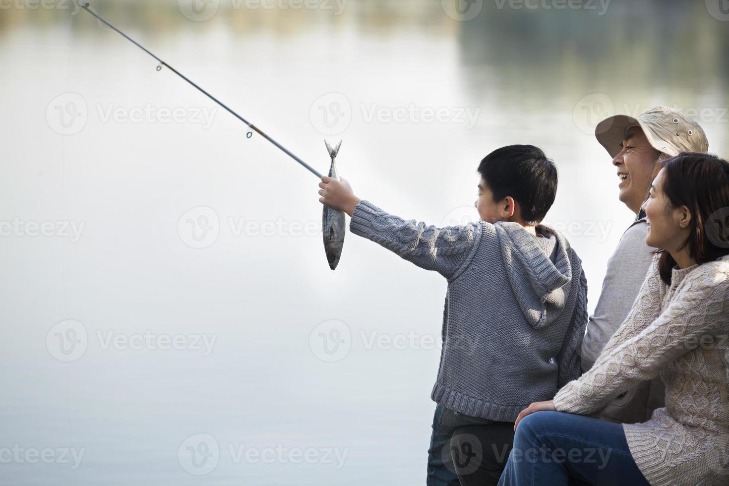 ragazzo ammirando la pesca con la famiglia al lago foto