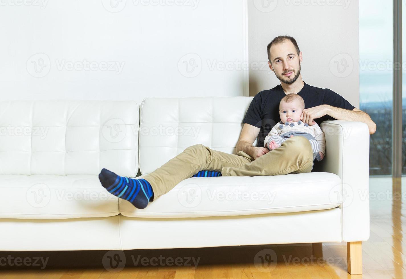 padre con bambino sul divano che si divertono foto