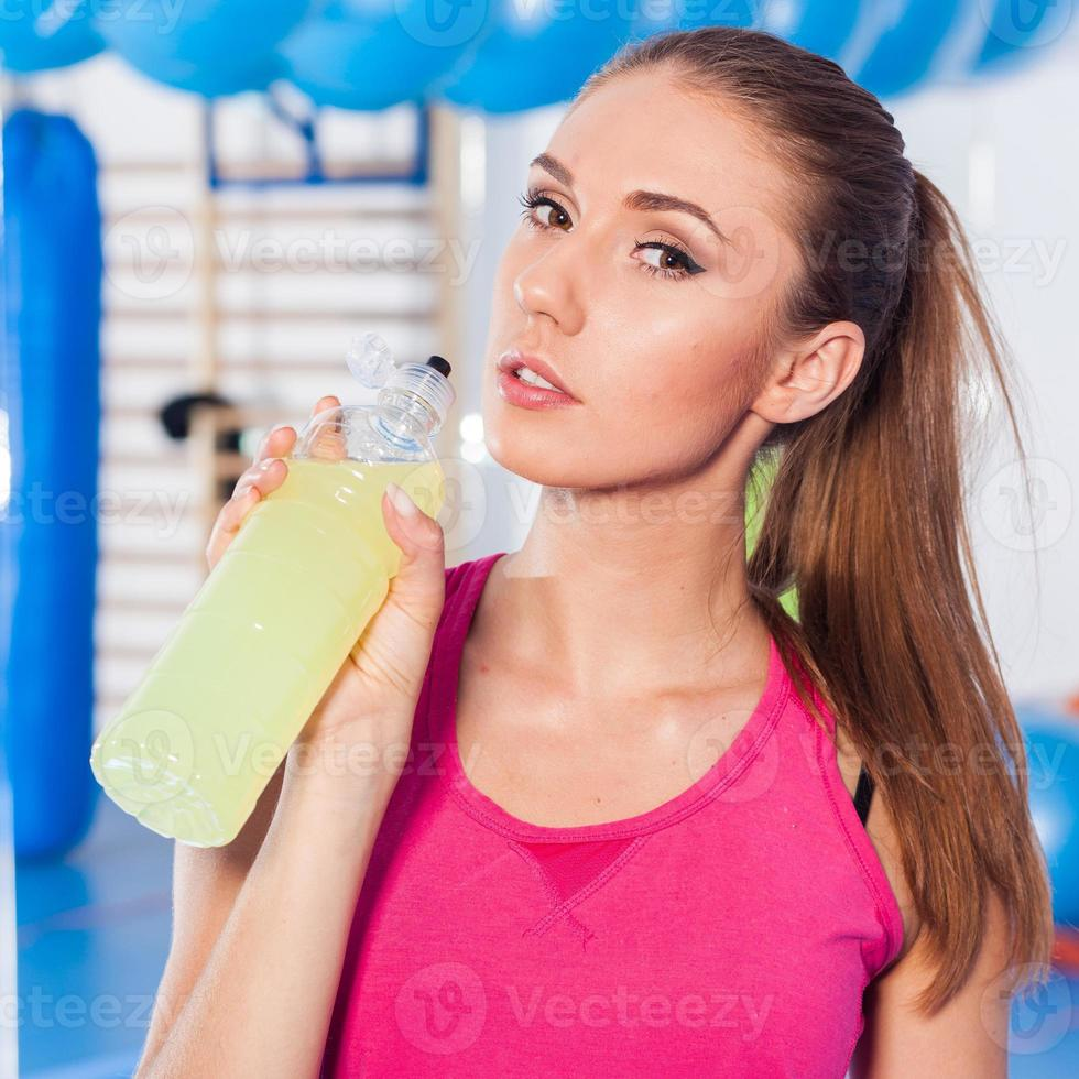 ragazza che beve bevanda isotonica, palestra foto