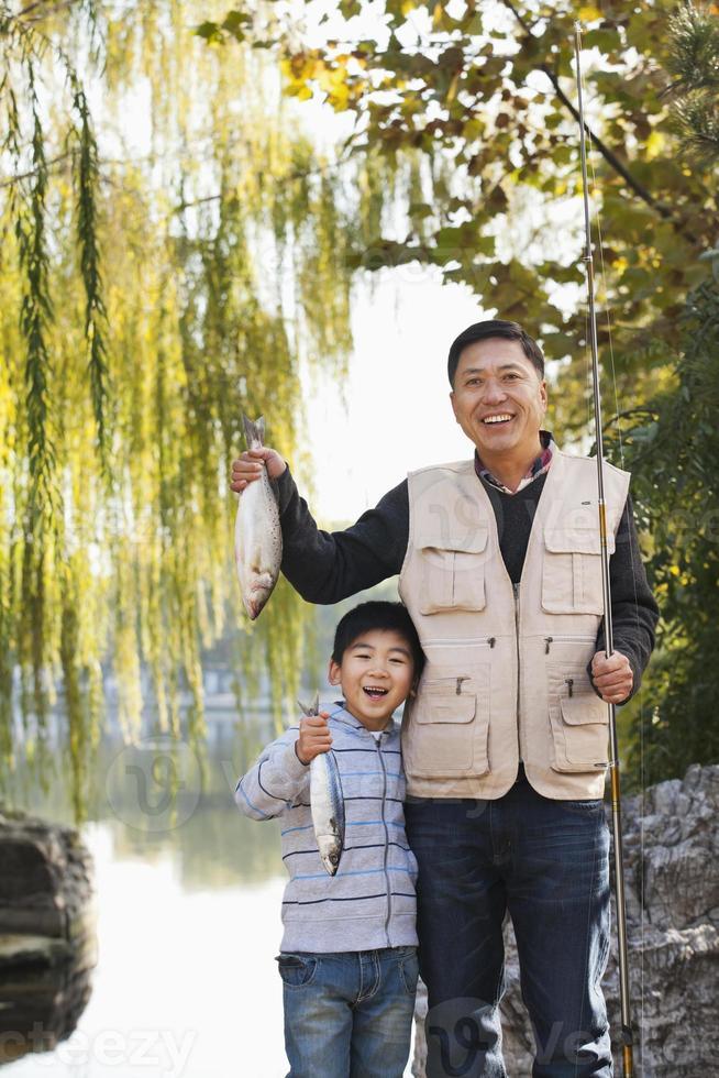 padre e figlio che mostrano la pesca pescata nel lago foto
