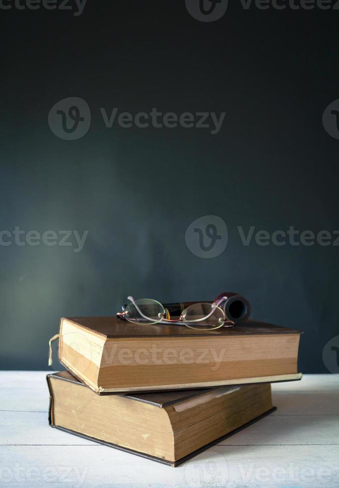 occhiali e tubo di fumo sul vecchio dizionario foto
