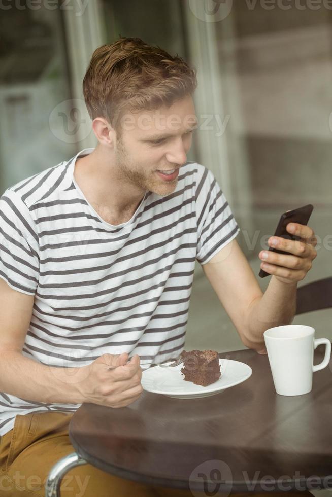 studente sorridente con la torta al cioccolato tramite smartphone foto