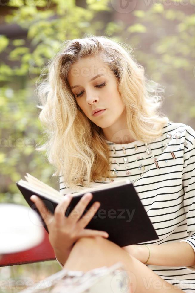giovane studentessa che studia al parco foto