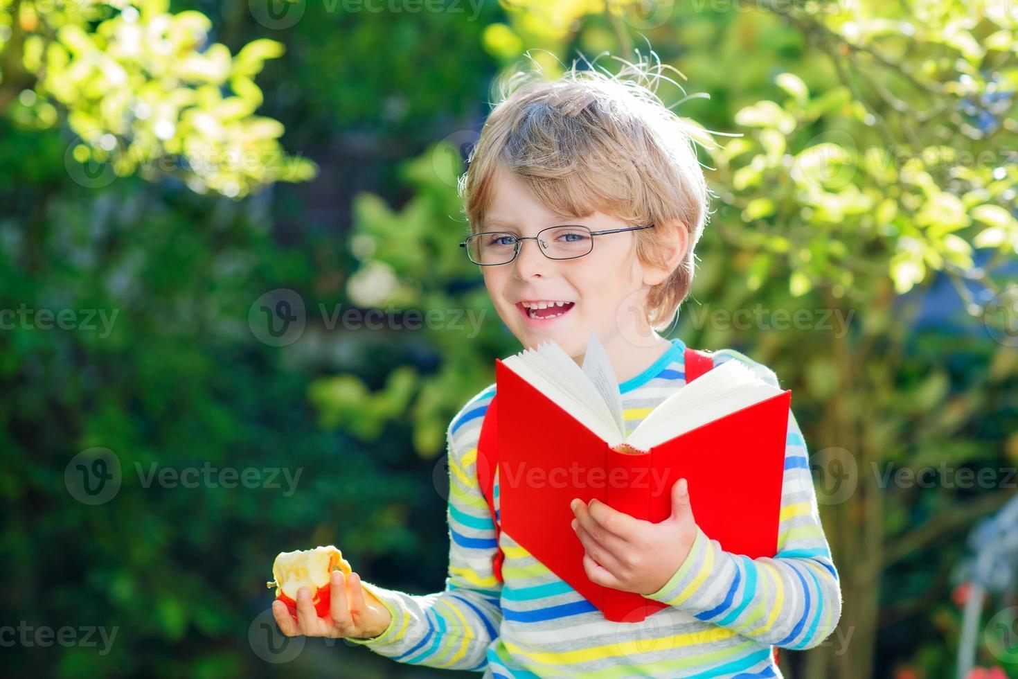 ragazzino con mela sulla strada per la scuola foto
