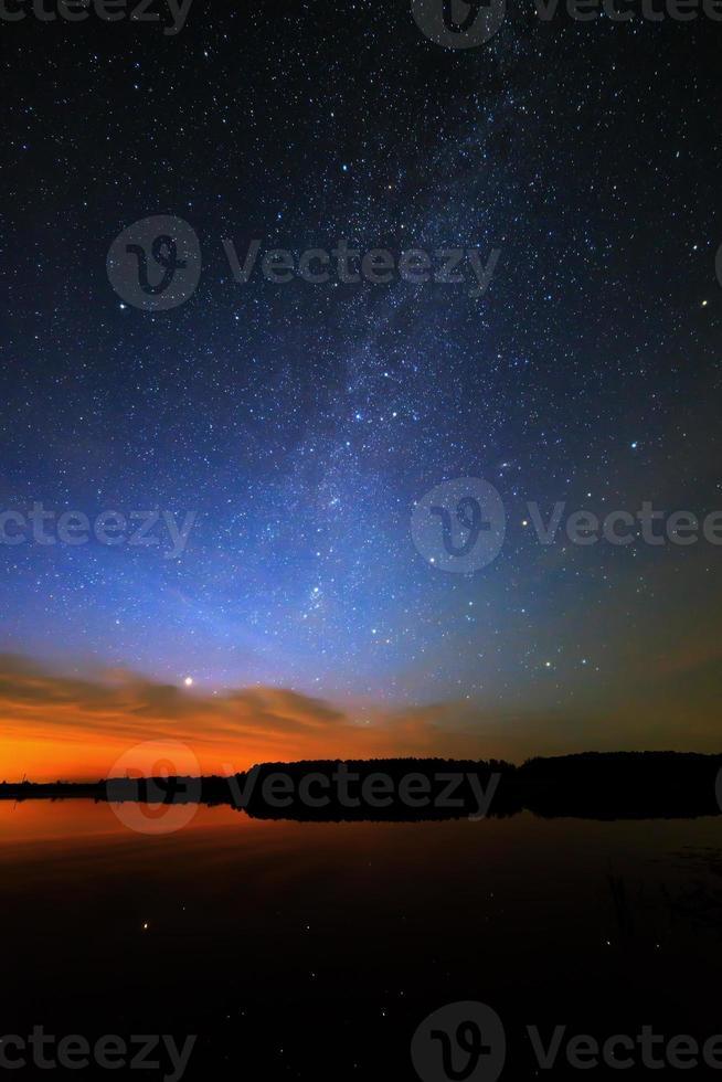 alba del mattino su sfondo stellato cielo riflessa nell'acqua foto
