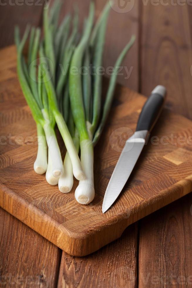 coltello, mazzo di cipolle e tagliere foto