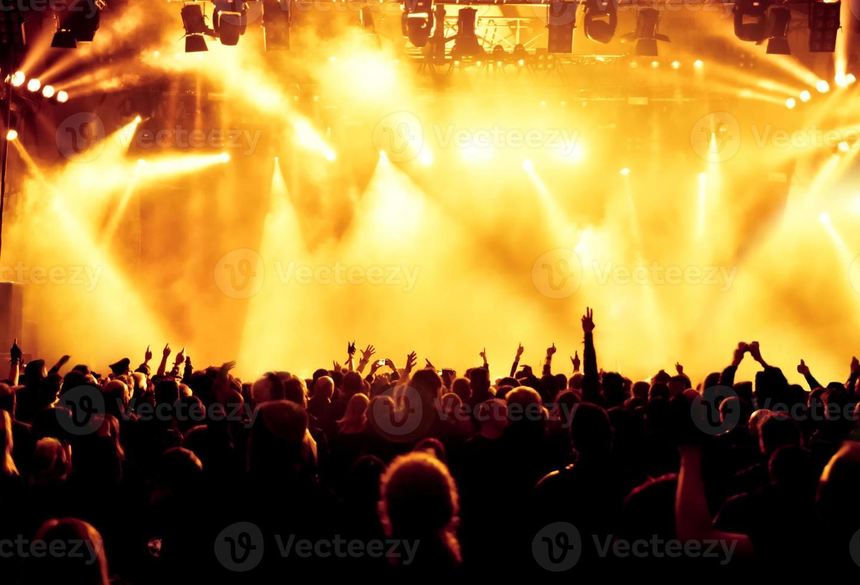 una folla ad un concerto con luci gialle e nebbia foto