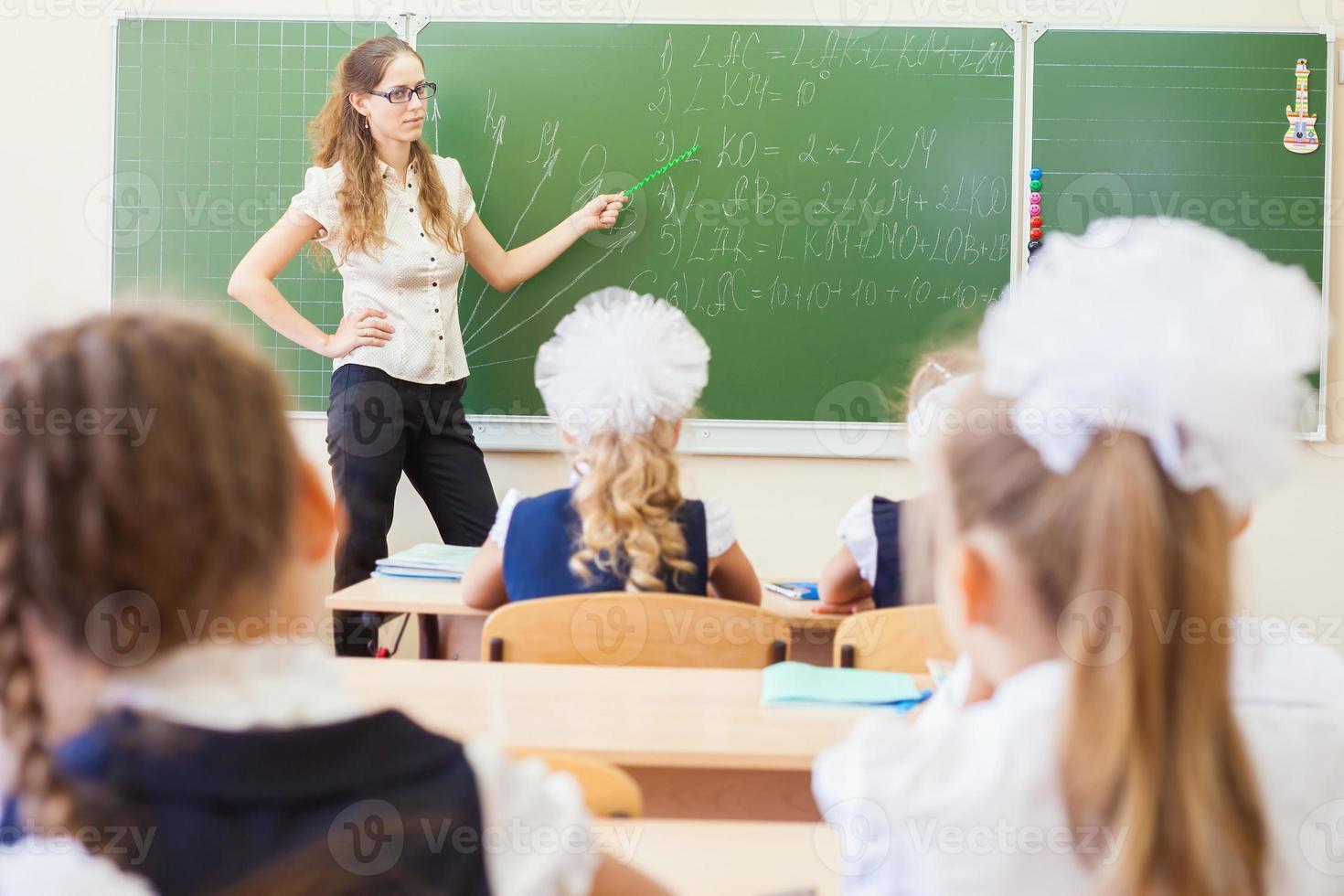 insegnante vicino lavagna insegnare ai bambini la matematica o la geometria, tenendo il puntatore. foto