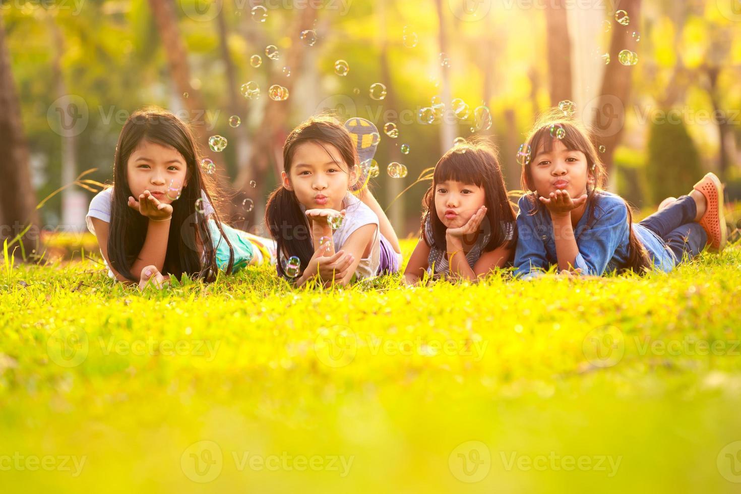 bambini carini divertirsi bolla sul prato verde foto