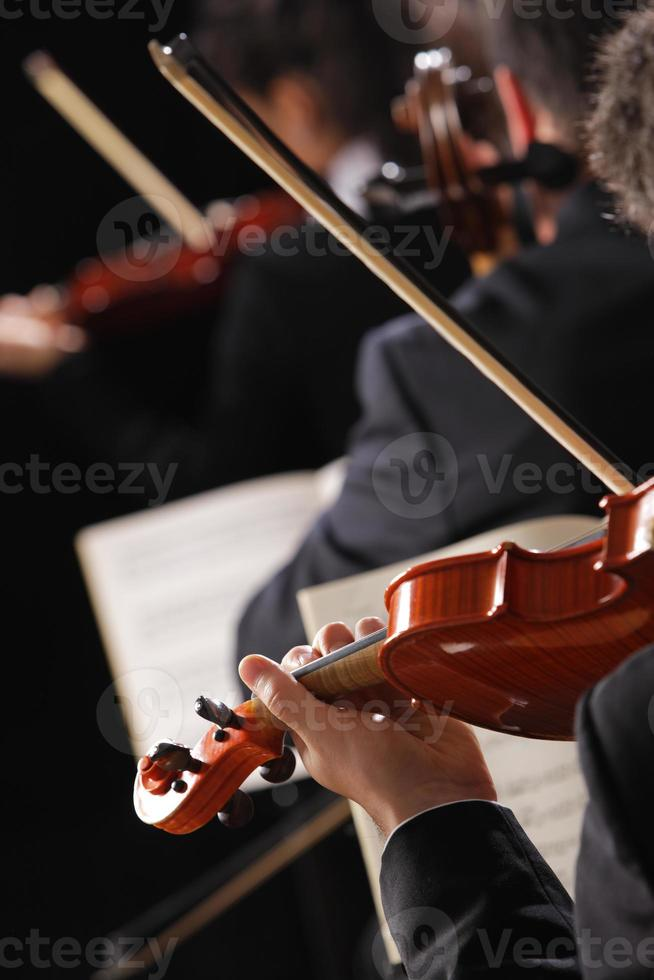 primo piano da dietro di un violinista in un'orchestra sinfonica foto