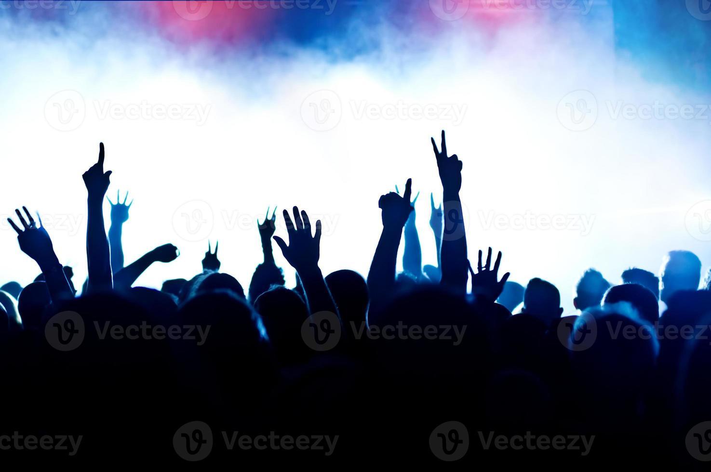 folla di concerti stagliata da luci del palcoscenico e fumo foto