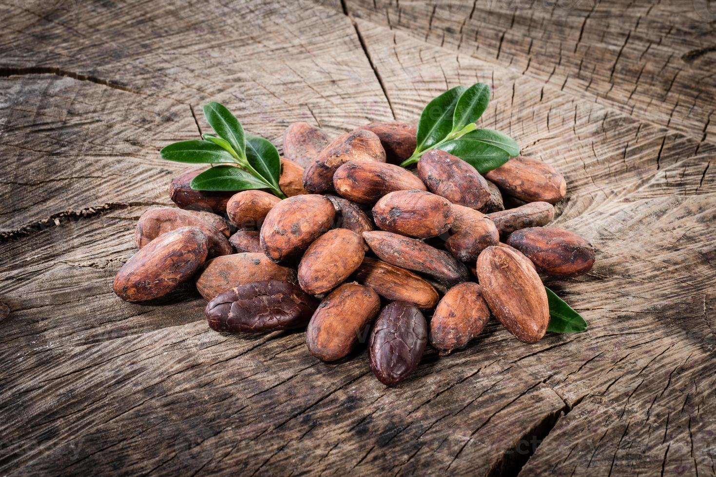 fave di cacao su fondo di legno foto