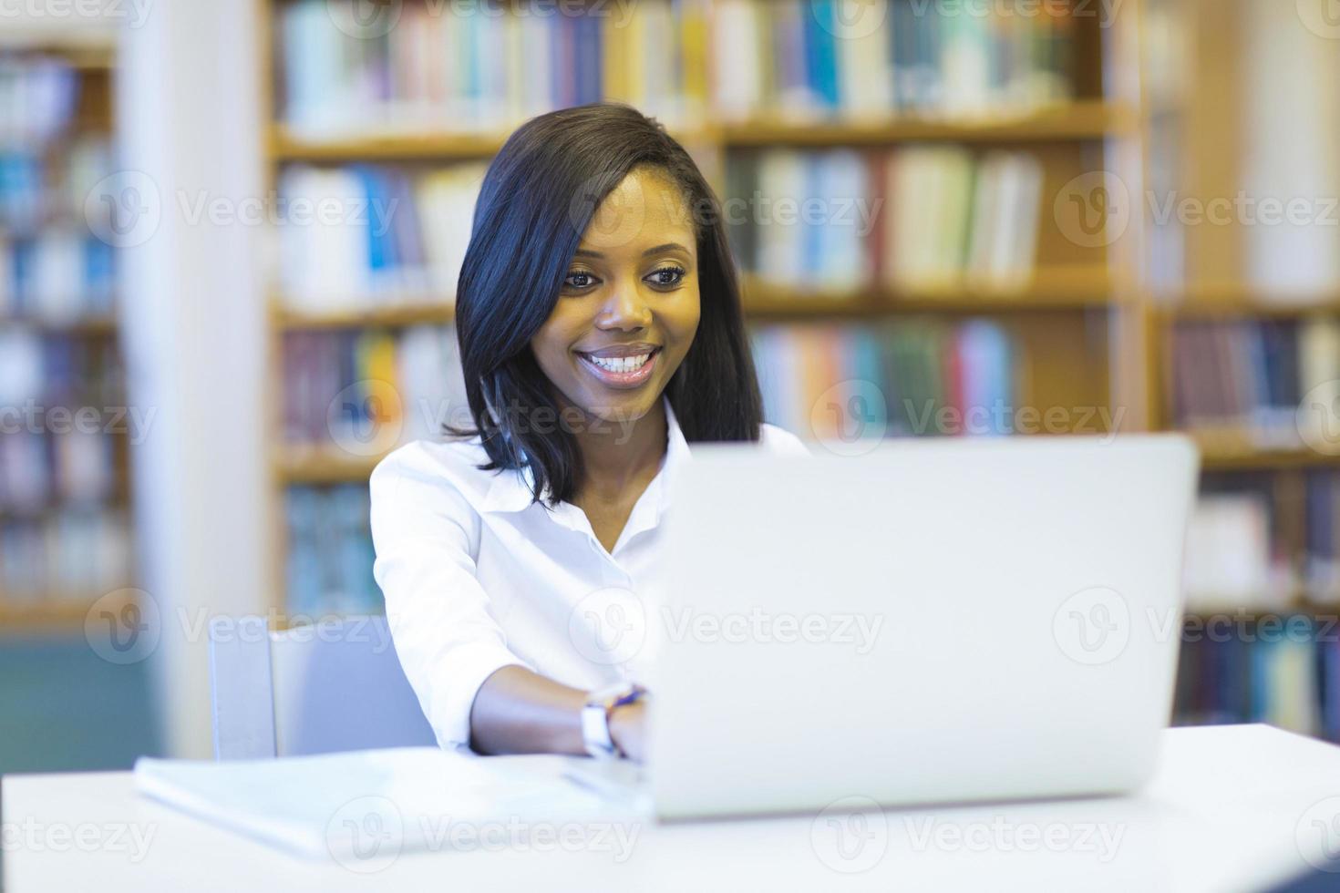 studente di college afroamericano femminile che per mezzo del computer portatile foto