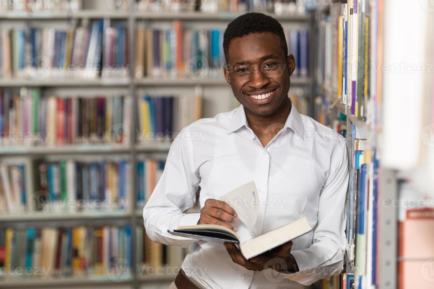 bel giovane studente universitario in una biblioteca foto