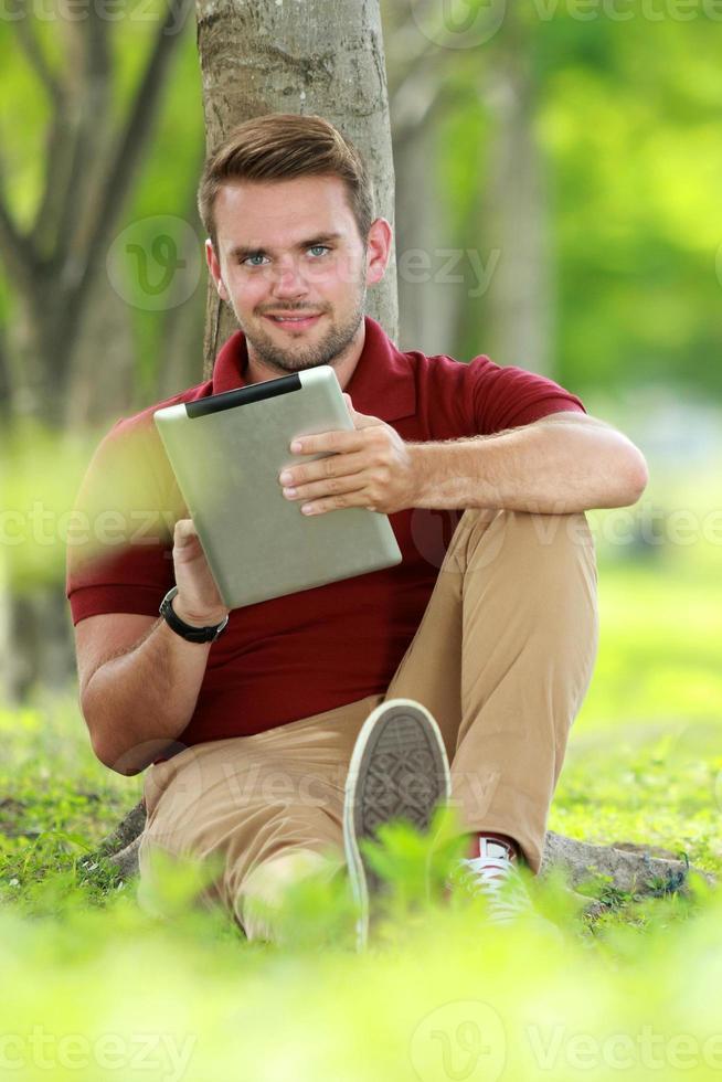 studente di college che naviga in Internet utilizzando il tablet foto