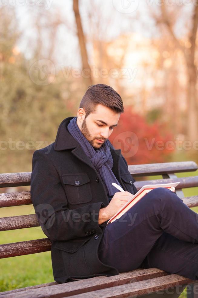 giovane che scrive su una panchina del parco foto