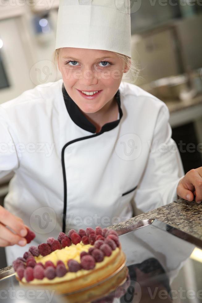 studente di cuoco pasticcere mettendo lamponi sulla torta foto