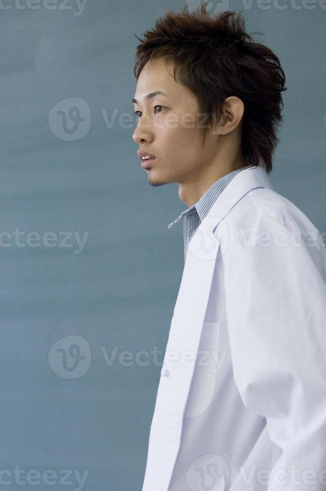 studente maschio che indossa camice bianco foto