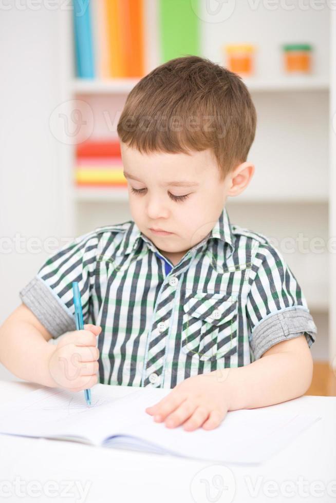 il ragazzino sta attingendo il libro bianco foto