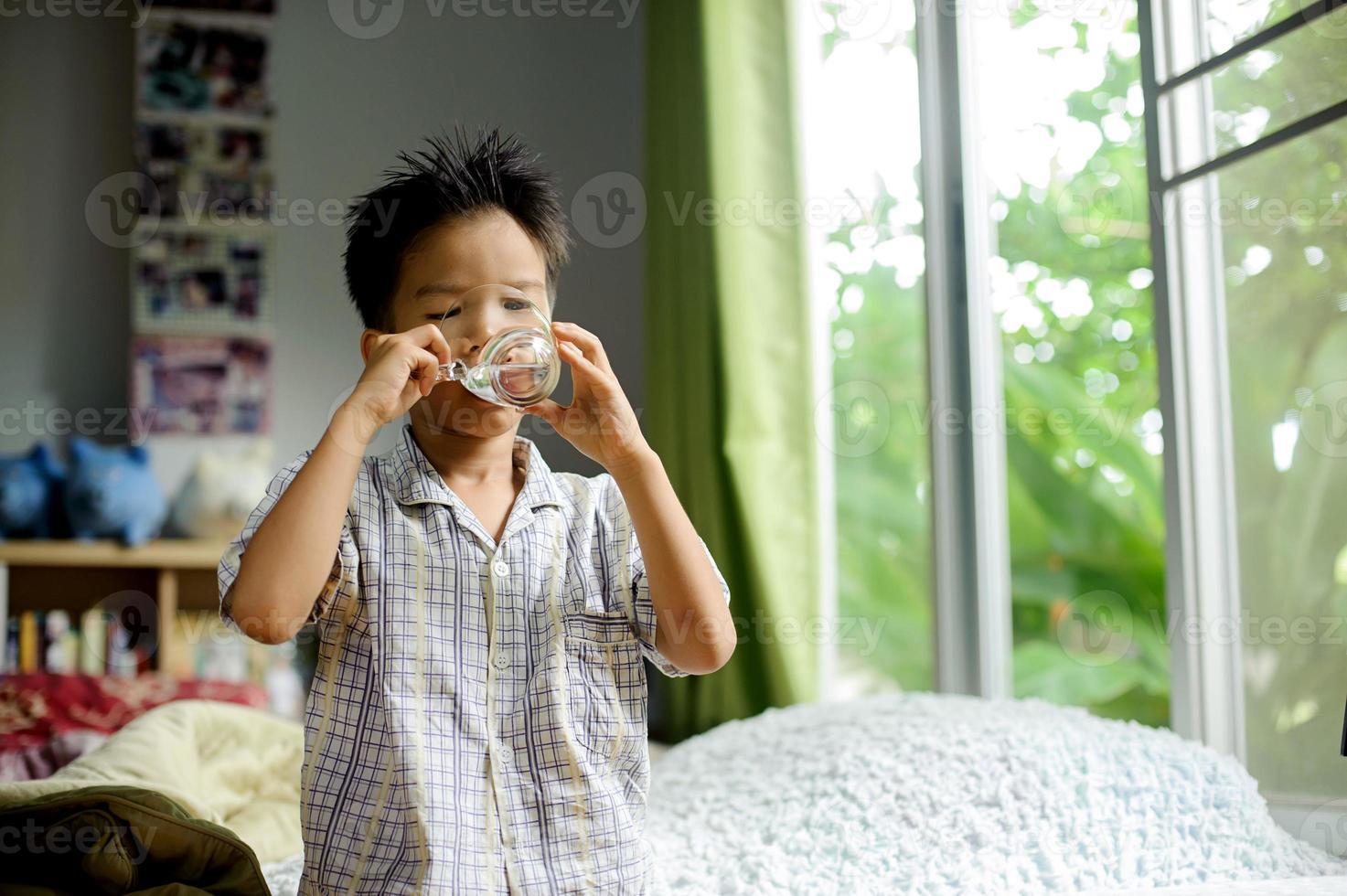 ragazzo bere acqua dal bicchiere foto