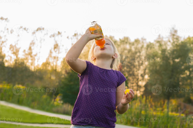 la ragazza beve il succo dalla bottiglia foto