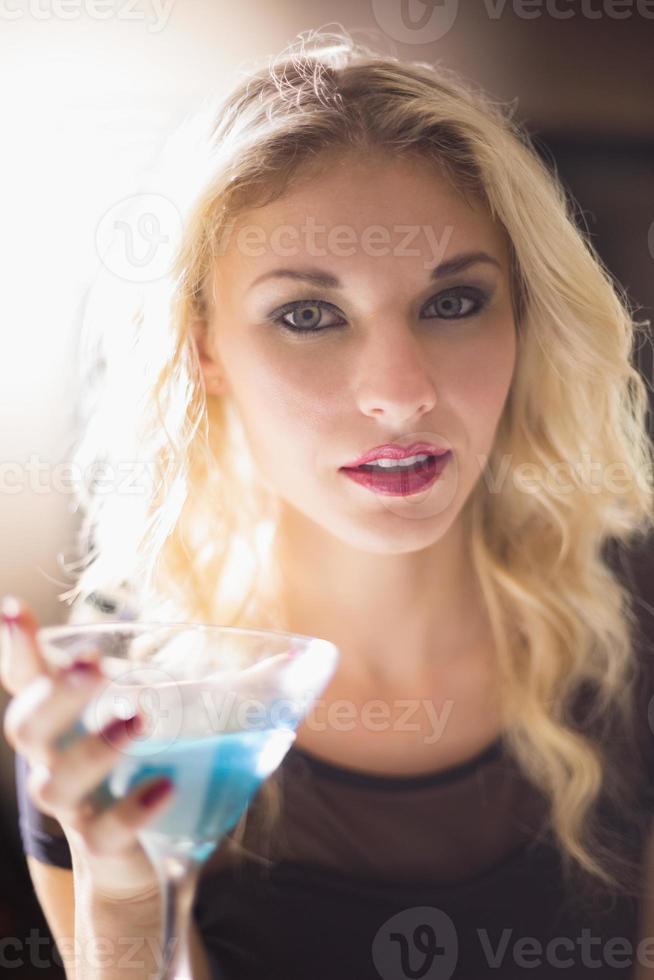 bionda attraente che beve un cocktail foto