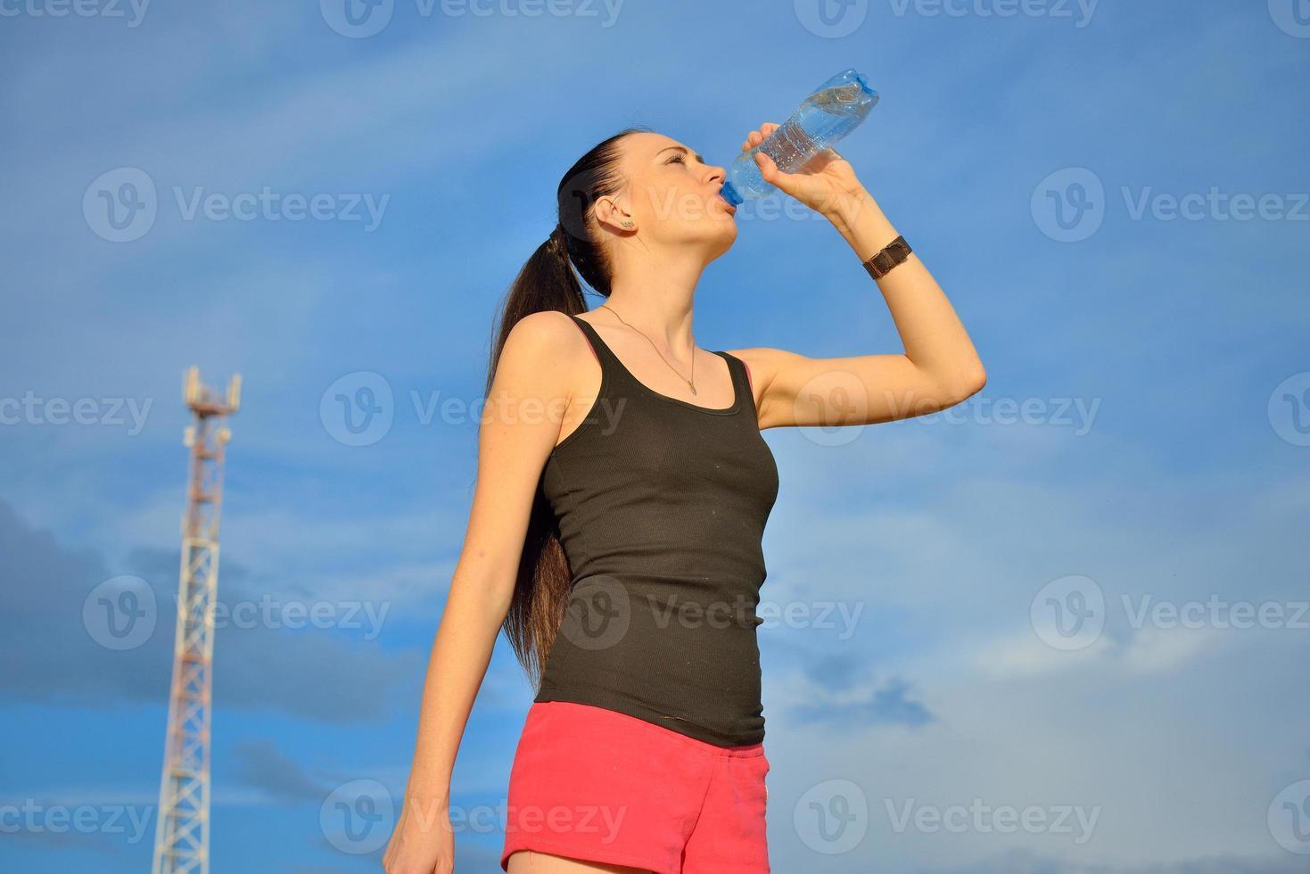 donna acqua potabile dalla bottiglia foto