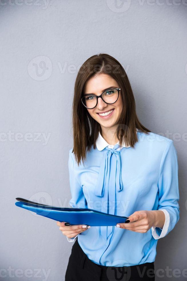 donna di affari allegra con le cartelle sopra fondo grigio foto