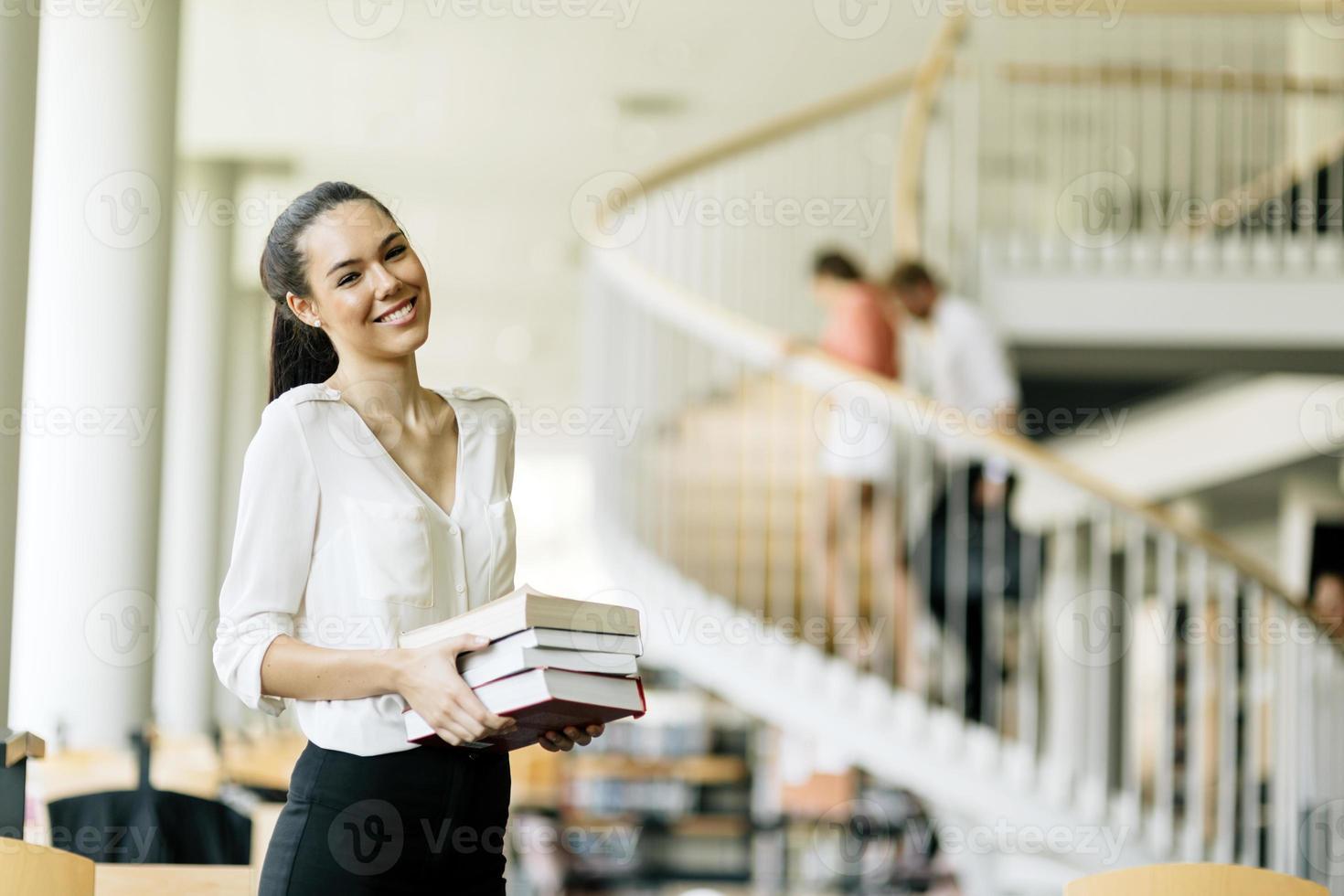 bella donna con libri in una biblioteca foto