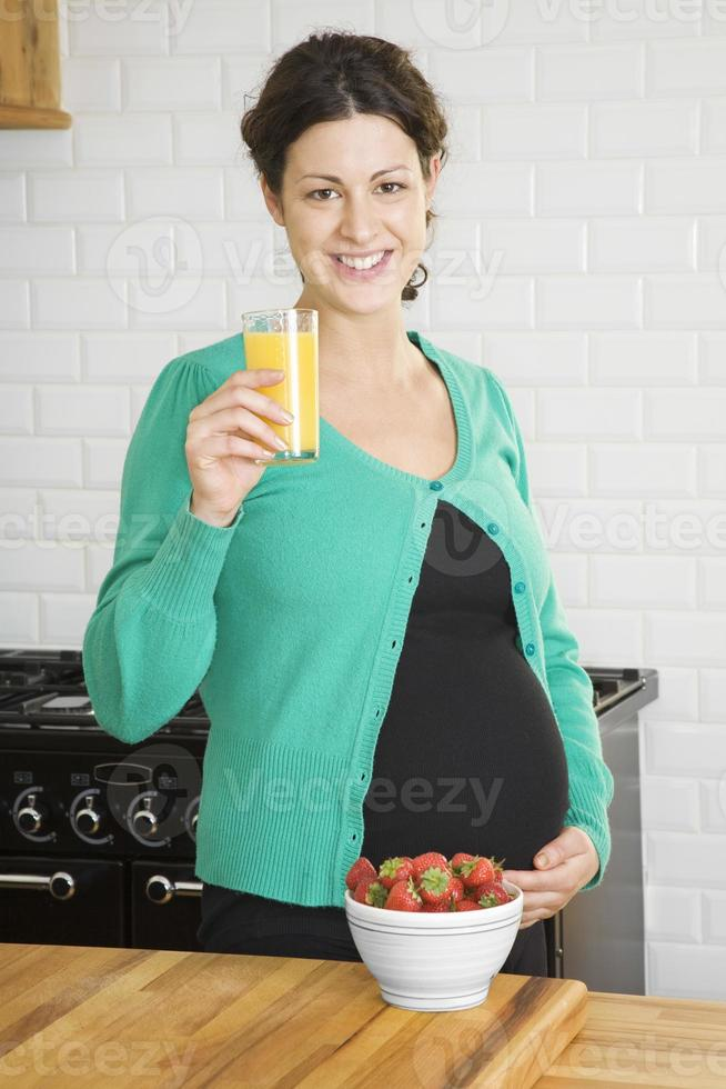 donna incinta che beve il succo di frutta foto