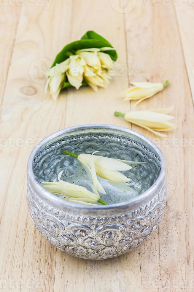 bere acqua con fiori di champaka. foto