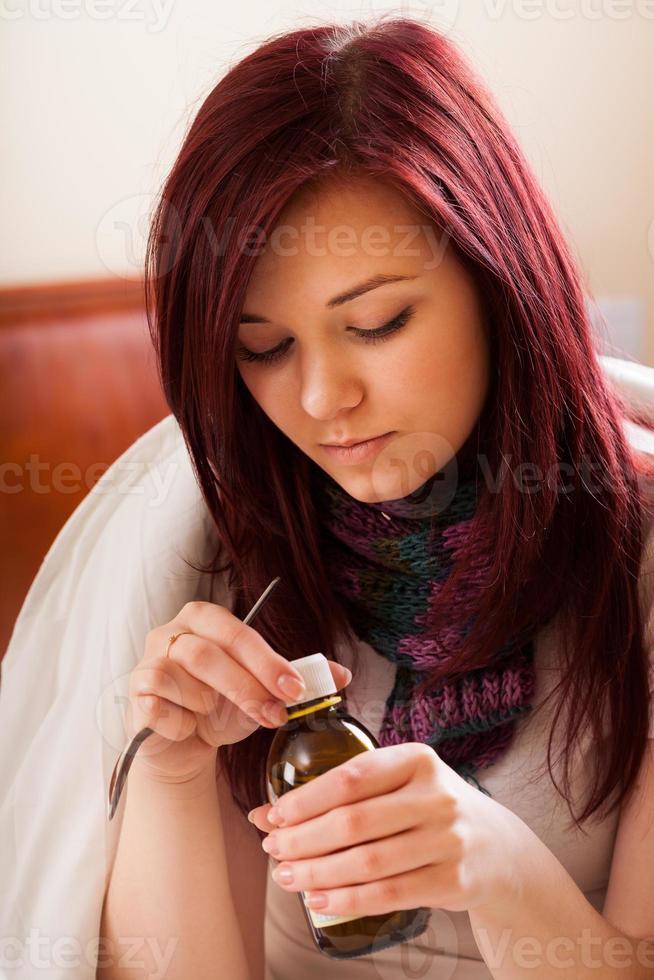 donna con influenza che beve sciroppo foto