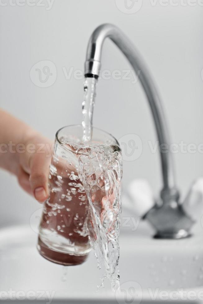 bicchiere versando acqua fresca da bere foto