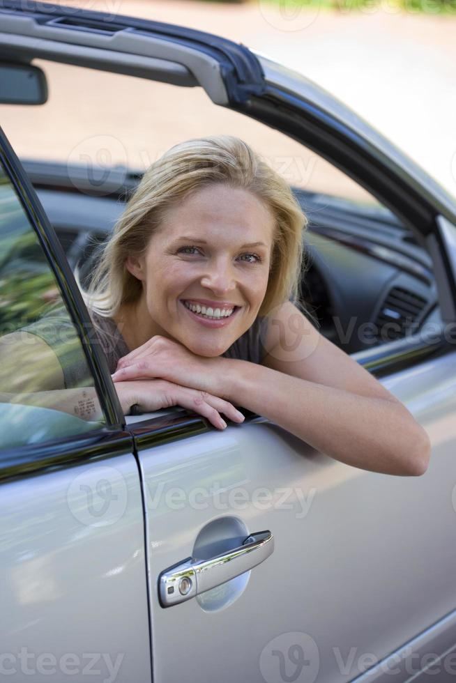 donna seduta nel sedile di guida di auto parcheggiata sul vialetto foto