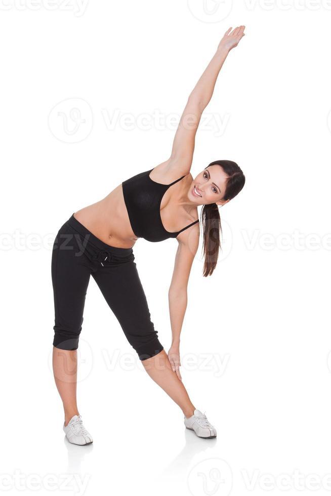 stiramento felice della giovane donna foto