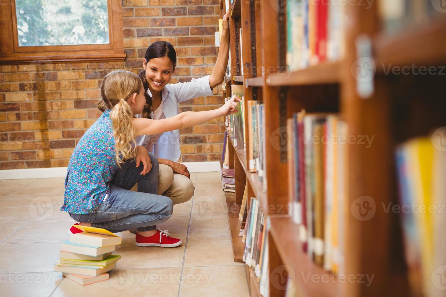 insegnante e bambina che selezionano libro in biblioteca foto
