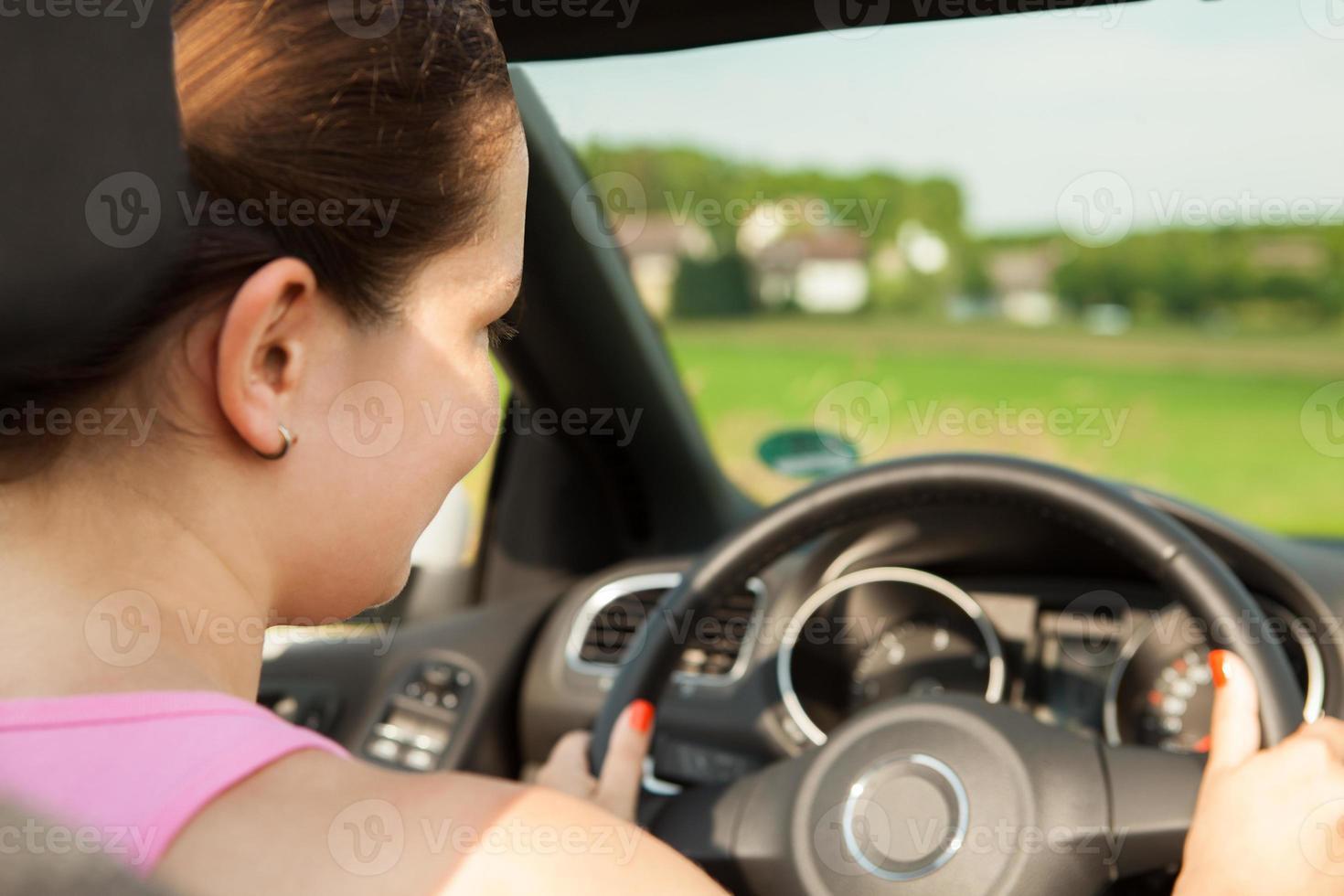 felice giovane donna alla guida dell'auto foto