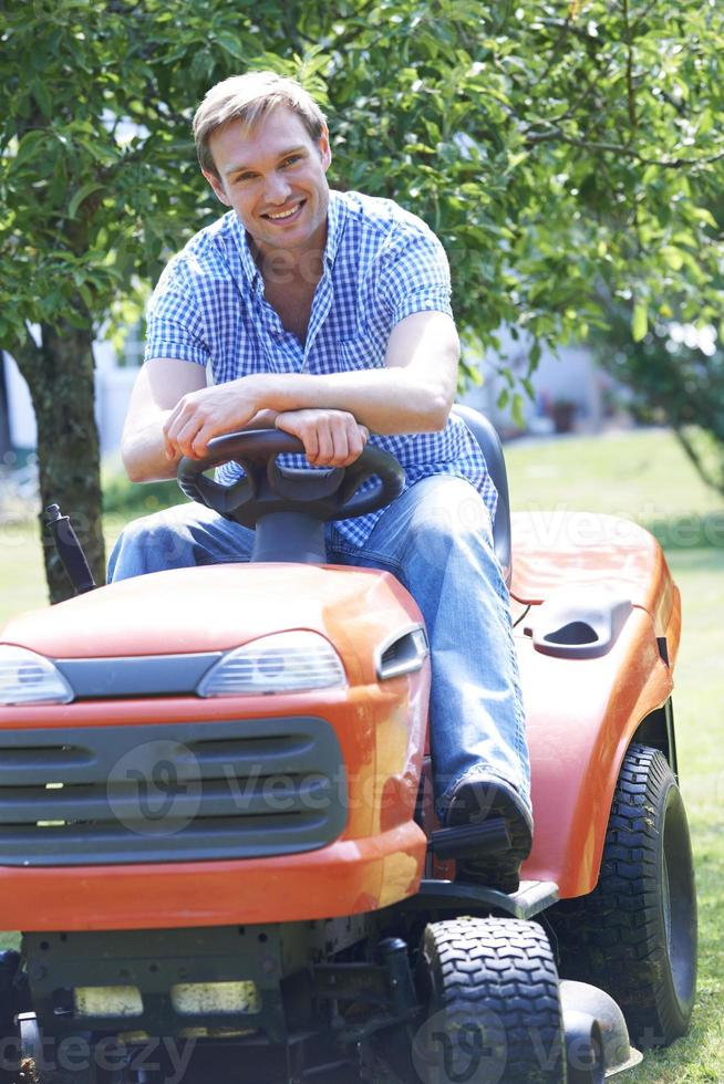 uomo taglio erba utilizzando sedersi sul tosaerba foto
