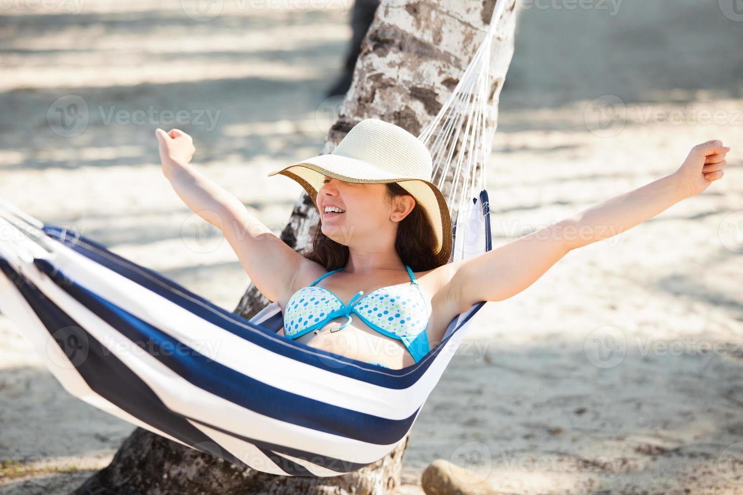 donna che allunga in amaca in spiaggia foto