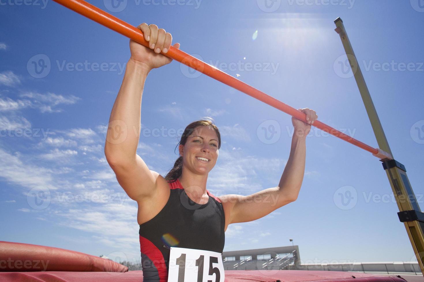 giovane atleta femminile con le mani sulla barra (riflesso lente) foto