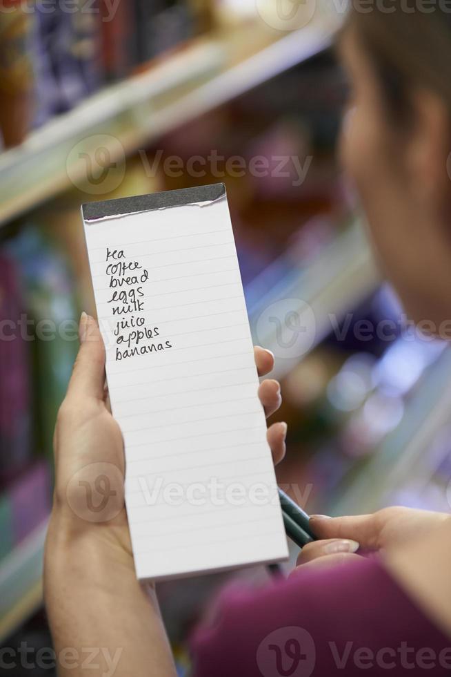 donna che legge la lista della spesa in un supermercato foto